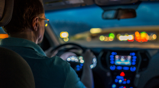 man driving a car wearing glasses