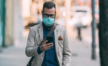 men with face mask and eyeglasses walks while using cellphone