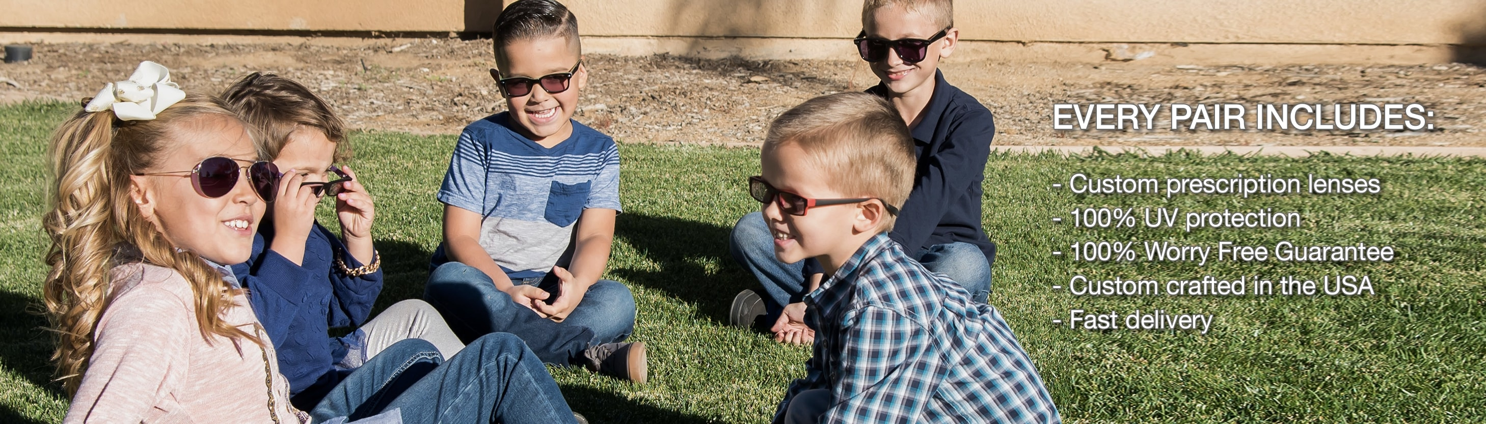 5 children wearing sunglasses, sitting on the grass laughing and playing.