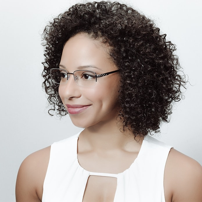 Brunette woman with curly hair wearing rimless rectangle eyeglasses
