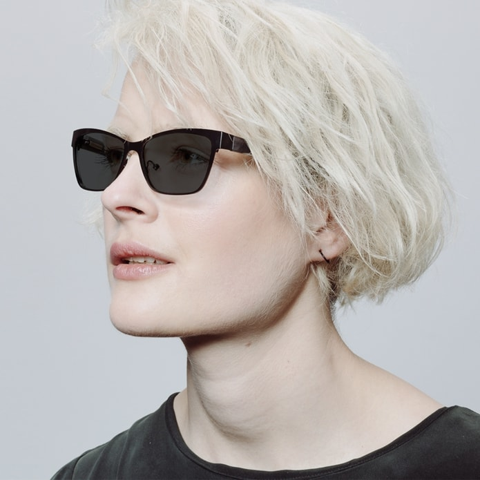 Blonde woman with short hair wearing metal cateye sunglasses with gray tint