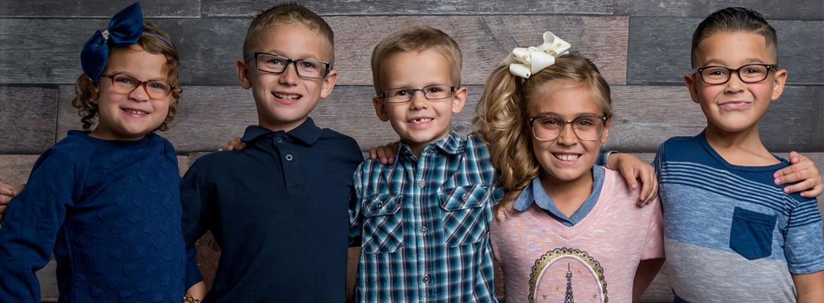Group of young kids smiling and wearing glasses