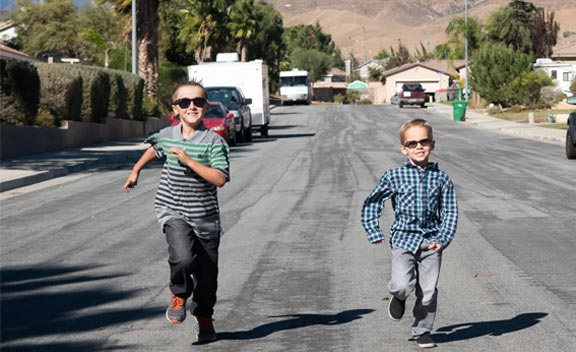 two boys running and wearing glasses