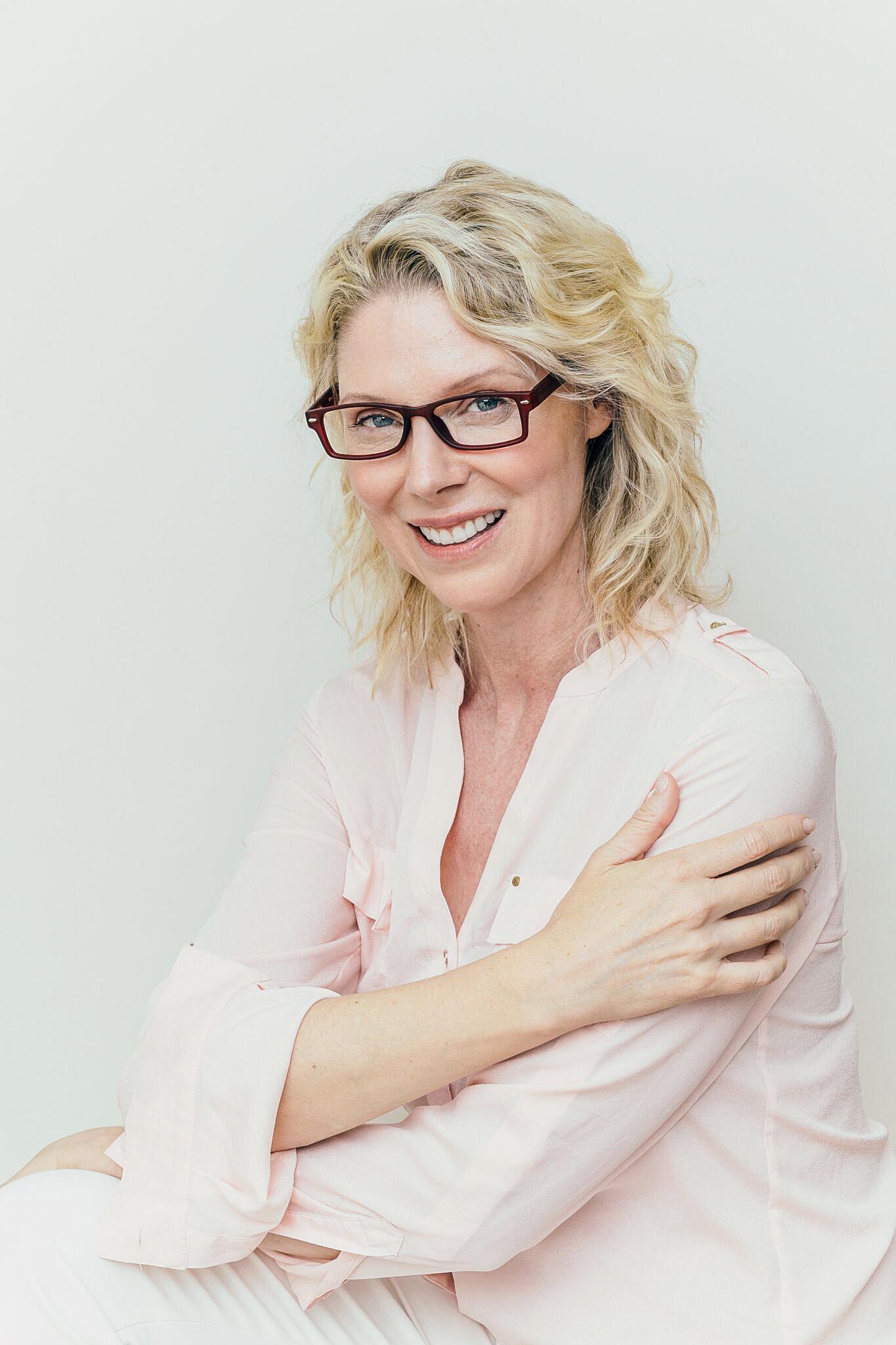 blonde woman wearing matte red glasses