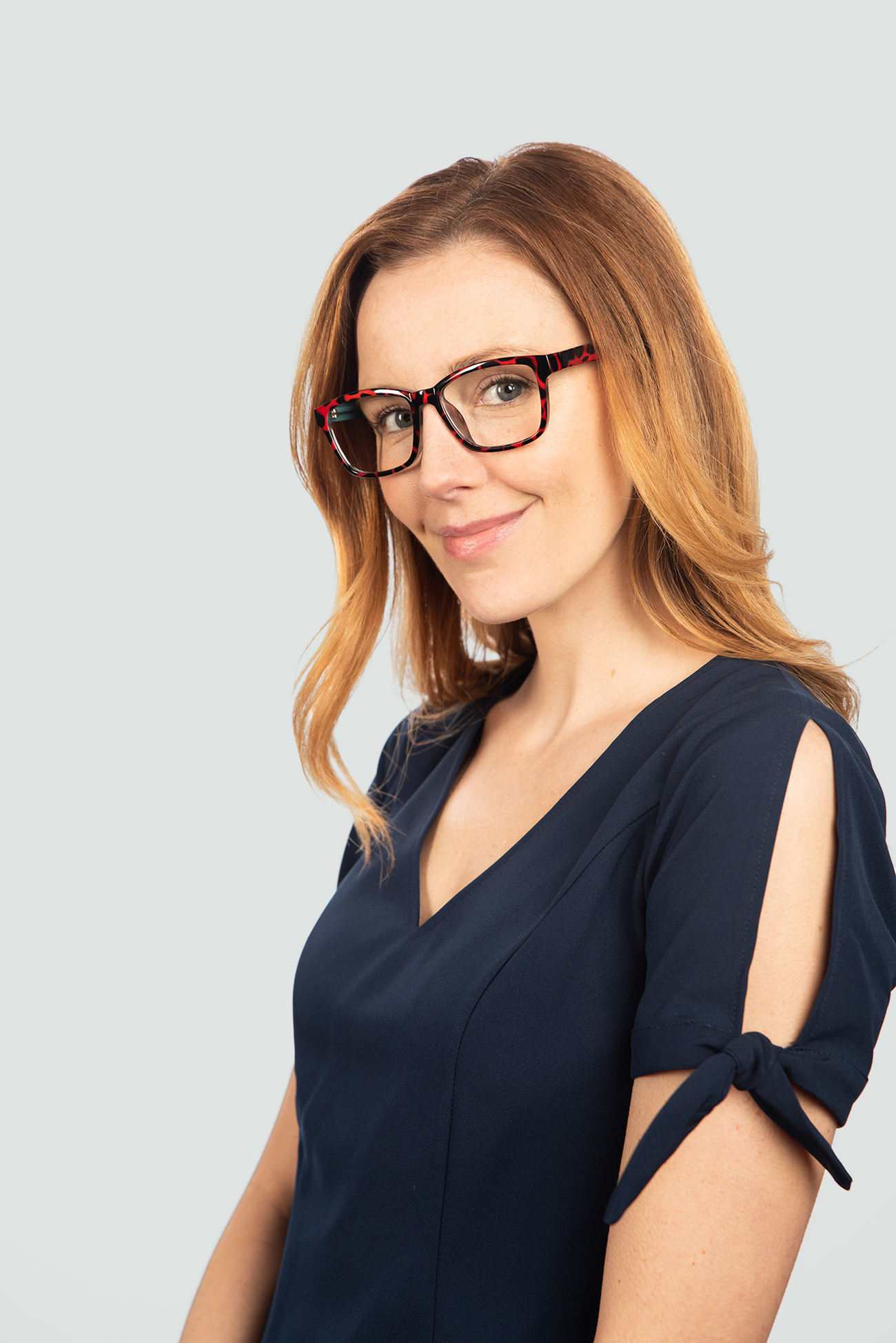 red head woman wearing black and red plastic glasses