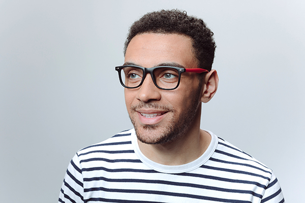 black haired man wearing matte red glasses