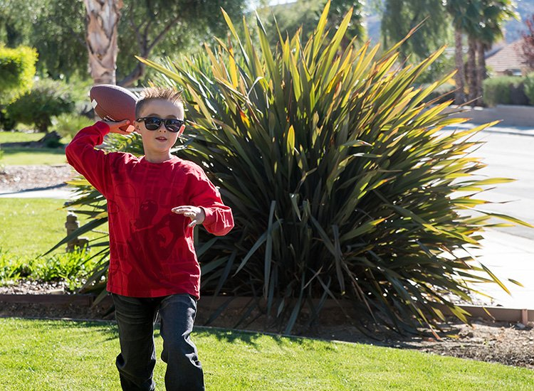 boy wearing sunglasses and throwing a football