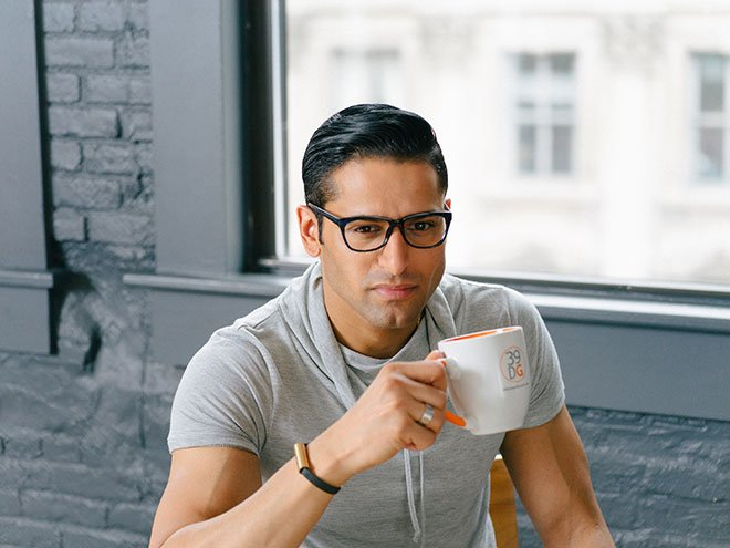 black haired man wearing black glasses and drinking from a cup in his apartment