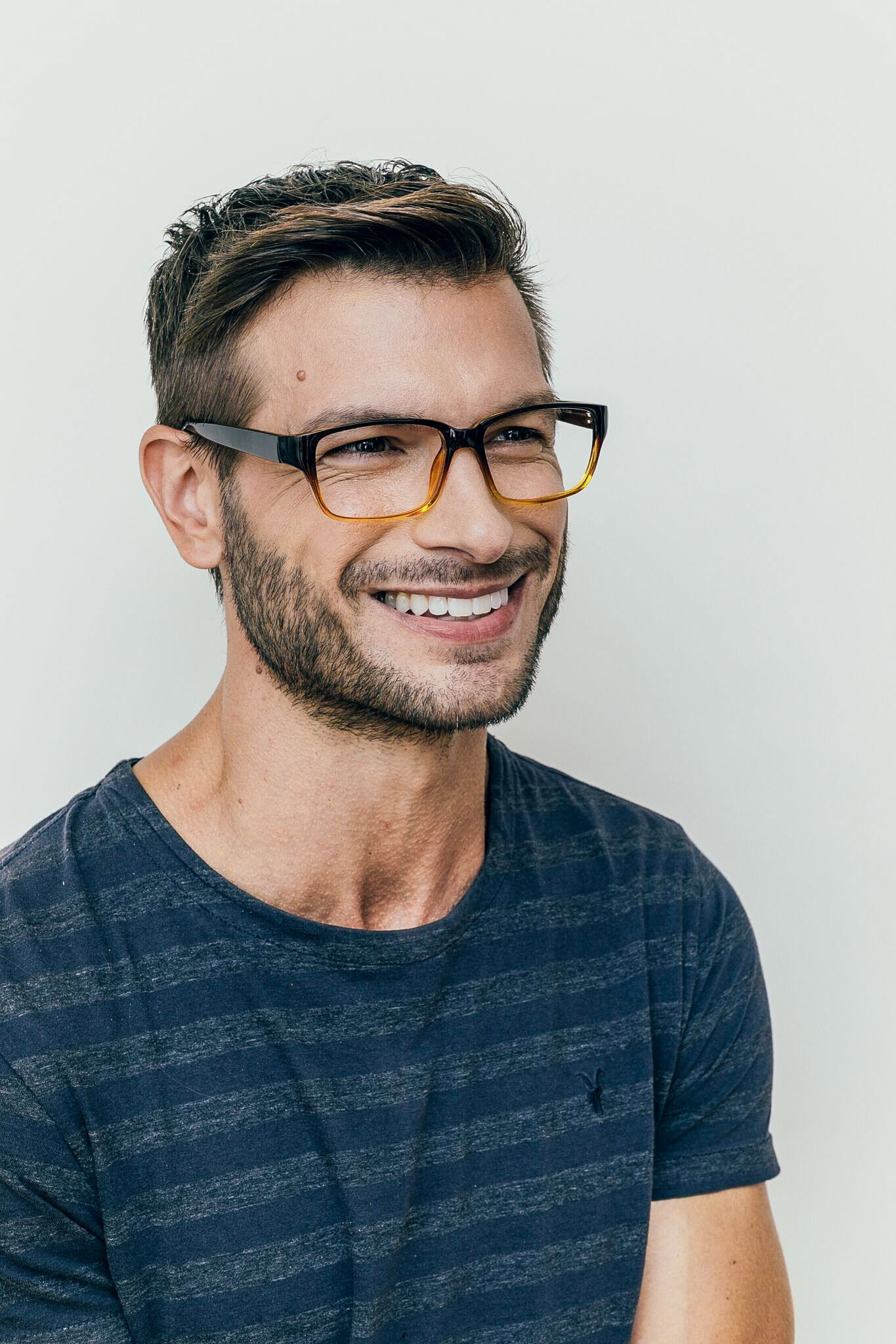 brunette man wearing plastic black and brown fade glasses