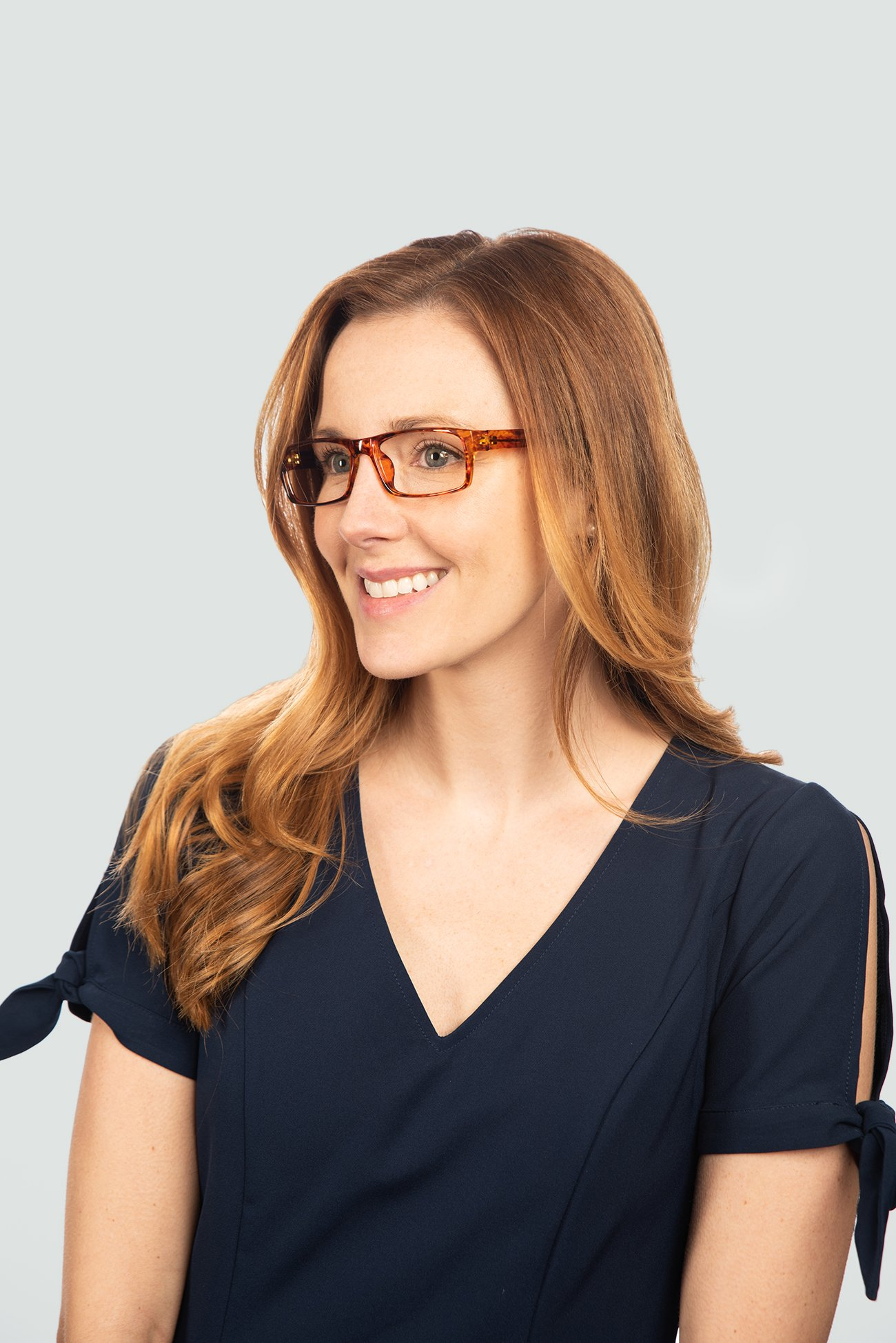 red head woman wearing plastic tortoise glasses